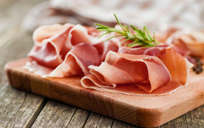 Behind a slice of prosciutto